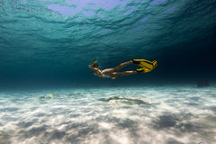 Woman freediver. Explores tropical underwater world, glides over sandy bottom Stock Photo