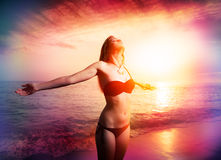 Woman in freedom in sunset on the beach Stock Photo