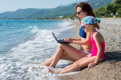 Woman freelancer on the beach with a laptop, free space. Mom and daughter are relaxing together, summer vacation. Remote work. Woman freelancer on the beach with stock images