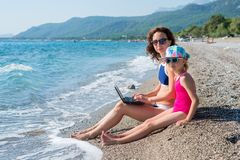 Woman freelancer on the beach with a laptop, free space. Mom and daughter are relaxing together, summer vacation. Remote work. Woman freelancer on the beach with stock photography