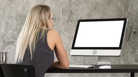 Woman freelancer looking at computer monitor. White Display. View to the screen of computer. Woman freelancer looking at computer monitor. White Display stock video footage