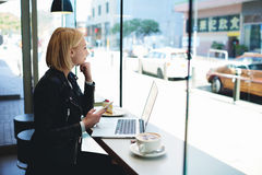 Woman freelancer is using cell phone and net-book Stock Photos