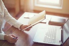 Woman freelancer working at home telework taking notes. Royalty Free Stock Images