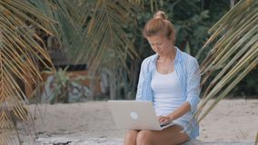 Woman freelancer works on the beach. Young woman sitting on a log with a laptop overlooking the sea. Woman freelancer works on the beach stock video footage