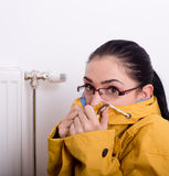 Woman freezing next to radiator Stock Images
