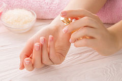 Woman with French manicure applies perfume on wrist royalty free stock photography