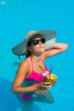 Woman with fresh cocktail in the swimming pool Royalty Free Stock Image