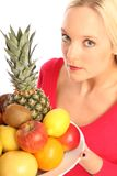 Woman with fresh fruits. Young blond woman holding a plate with different fresh fruits stock photography