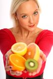 Woman with fresh fruits. Young blond woman holding different fresh fruits royalty free stock photography