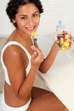 Woman with fresh fruits. Beautiful brunette woman eating some fresh fruits royalty free stock images