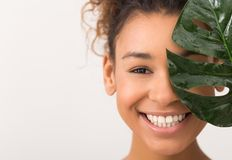 Woman with fresh leaf covering half of face. African-american woman with fresh leaf covering half of face on white background with copy space stock photo