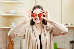 Woman with fresh tomatoes. Happy woman holding two fresh tomatoes in front of her eyes Royalty Free Stock Images