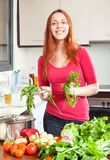 Woman with fresh vegetables and greens in kitchen Stock Image