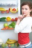 Woman and fridge. Woman looking for something in the fridge at home stock image