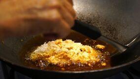 Woman fried batter fish in a hot olive oil on a frying pan