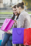 Woman with friend looking into shopping bag outdoors Royalty Free Stock Image