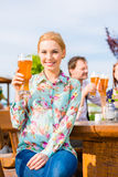 Woman with friends in beer garden Royalty Free Stock Photos