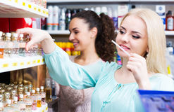 Woman friends buying perfume Royalty Free Stock Photos