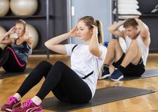 Woman With Friends Doing Situps In Gym. Young women with male and female friends doing situps in gym Stock Photography
