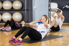 Woman With Friends Doing Situps In Gymnasium Stock Photography
