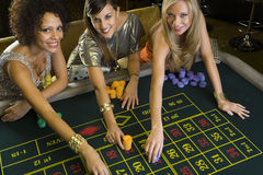 Woman and friends placing gambling chips on roulette table, portrait, elevated view Royalty Free Stock Photos