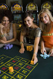 Woman and friends placing gambling chips on roulette table, portrait, elevated view Royalty Free Stock Images