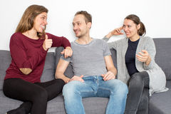 Woman with friends and thumb up on a sofa. Three persons with good news stock photos