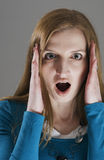 Woman in fright. Head and shoulder of younng blond woman with head ache and fingers at the temple mouth open Stock Image