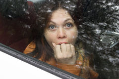 Woman in fright. Frightened woman in a car behind the glass in the back seat closeup eyes closed mouth hand Royalty Free Stock Images