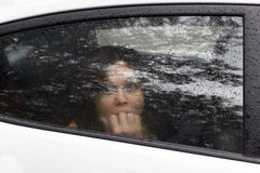 Woman in fright. Frightened woman in a car behind the glass in the back seat closeup eyes closed mouth hand Stock Photography