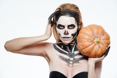 Woman with frightened skeleton makeup holding pumpkin Stock Images