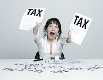 Woman frightened by taxes. Young desperate woman at her desk showing terrible tax bills to the camera while shouting out royalty free stock images