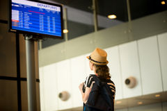 Woman in front of airport flight information panel Stock Images