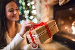 Woman in front of Christmas tree holding present. Royalty Free Stock Photography