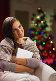 Woman in front of Christmas tree hugging tablet PC Royalty Free Stock Photography