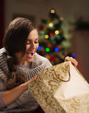 Woman in front of Christmas tree looking in bag Royalty Free Stock Image