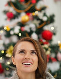 Woman in front of Christmas tree looking up Royalty Free Stock Image