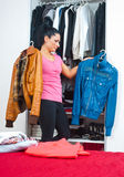 Woman in front of closet full of clothes royalty free stock image