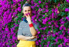 Woman in front of colorful magenta flowers bed having fun time. Colorful Freshness. smiling trendy woman in yellow shorts and stripy shirt in the front of Royalty Free Stock Photos