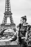 Woman in front of Eiffel tower in Paris, France looking aside. Bold winter in Paris. Portrait of modern woman in fur coat in the front of Eiffel tower in Paris Royalty Free Stock Photos