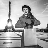 Woman in front of Eiffel tower in Paris holding shopping bag. Bright in Paris. smiling elegant woman in red coat in the front of Eiffel tower in Paris, France Royalty Free Stock Photography