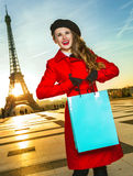 Woman in front of Eiffel tower in Paris holding shopping bag. Bright in Paris. smiling elegant woman in red coat in the front of Eiffel tower in Paris, France Stock Image