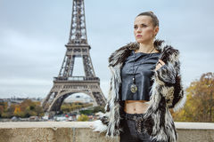 Woman in front of Eiffel tower in Paris looking into distance Stock Photo