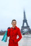 Woman in front of Eiffel tower with shopping bag looking aside Stock Photos