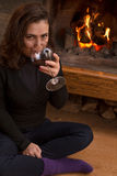 Woman in front of fireplace drinking red wine Royalty Free Stock Image