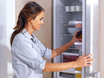 Woman in front of the fridge. Young woman in front of the fridge royalty free stock photography