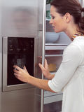 Woman in front of the fridge aa. Young woman in front of the fridge royalty free stock photos