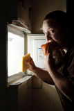 Woman in front of the fridge eating chicken Stock Photo