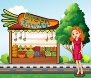 A woman in front of the green grocery stall Stock Image