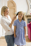 Woman in front hallway brushing young girl's hair Royalty Free Stock Photo